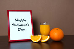 Red photo frame, orange juice and orange slice on wooden table Royalty Free Stock Images