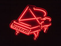 Red piano light. Neon light of a red grand piano stock photos