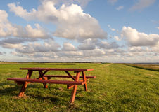 Red pick-nick table. On the grass along the sea near Tonder in Denmark against a blue sky with white clouds royalty free stock image