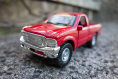 Red pick up truck toy on the road. Shallow depth of field Stock Image