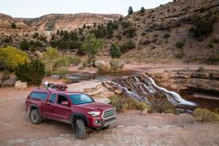 Free Red Pickup Camping Rig On Rocky Trail Near Waterfall In Southern Royalty Free Stock Photography - 102836107