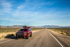 Red pickup camping truck travelling through the Nevada desert along the Extraterrestrial Highway. Red pickup truck loaded with overlanding and camping gear. The royalty free stock image