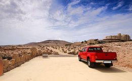 Red pickup on desert road. Fuerteventura, Canary Island, Spain Stock Images