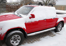 Red pickup with snow in driveway Royalty Free Stock Photo