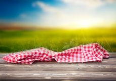 Red picnic cloth on wooden table mature bokeh background. Red picnic table cloth on wooden table empty space nature sunset field background.Food advertisment Royalty Free Stock Photos