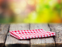 Red picnic cloth on wooden table mature bokeh background. Stock Photos