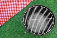 Red Picnic Tablecloth And BBQ Grill Appliance On The Lawn. Overhead View Of Red Picnic Tablecloth And Empty BBQ Grill Appliance On The Summer Green Lawn Stock Photo