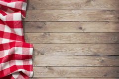 Red picnic tablecloth on wood table background. Red picnic tablecloth on left side of wooden table Royalty Free Stock Photo