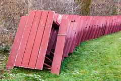 Red picnic tables stacked for winter storage in park. Royalty Free Stock Image