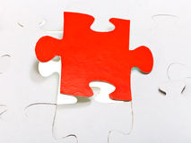 Red piece attached in assembled puzzles Royalty Free Stock Image