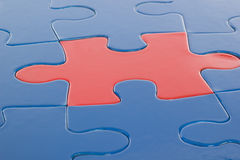 Red piece in blue puzzle Royalty Free Stock Images