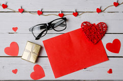 A red piece of paper and gift box on a white wooden background. Stock Photos