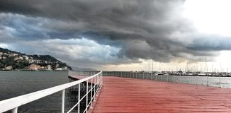 Red pier with stormy clouds to Rapallo Royalty Free Stock Image