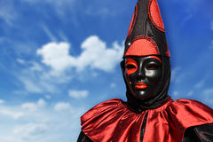 Red Pierrot carnival mask, with sky background and clouds, Venice, Italy Royalty Free Stock Images