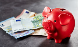Red piggy bank and Euro banknotes on gray surface Stock Image