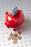 Red piggy bank with euro notes and coins Stock Photo
