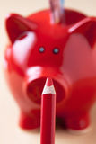 Red piggy bank and red pencil, close up, depth of field Stock Images