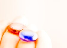 Red pill, blue pill. A red pill and a bule pill in hand Royalty Free Stock Photos