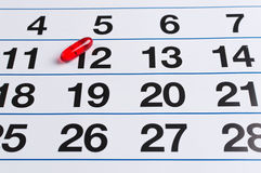 Red pill on the calendar. Schedule medication Royalty Free Stock Photography