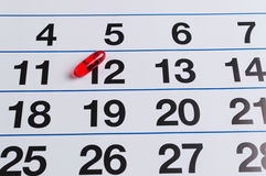 Red pill on the calendar. Schedule medication Stock Photography