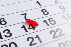 Red pill on the calendar. Schedule medication Stock Images