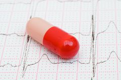 Red Pill on a Cardiogram Trace. Close up of a red capsule on a cardiogram monitor printout graph Stock Photos