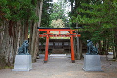 Red pillar in front of shrine and fox statue in Koyasan Wagayama Royalty Free Stock Image