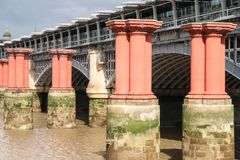 Red pillars in the River Thames between Blackfriars road bridge. And Blackfriars railway bridge. In 1923, railway services began to terminate at Waterloo and Royalty Free Stock Photos