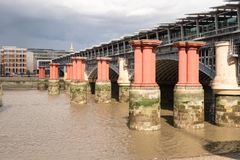 Red pillars in the River Thames between Blackfriars road bridge. And Blackfriars railway bridge. In 1923, railway services began to terminate at Waterloo and Stock Photography