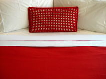 Red pillow. On bed with white sheet Royalty Free Stock Images