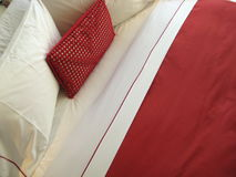 Red pillow. On bed with white sheet Stock Photo
