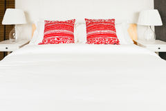 Red pillow on bedroom with white bed sheet and lamp Royalty Free Stock Photo