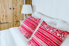 Red pillow on bedroom with white bed sheet and lamp Royalty Free Stock Photography