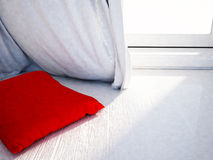 Red pillow near the window Stock Photo