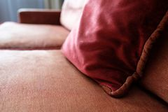 Red pillow on a sofa with armrest of upholstered furniture Royalty Free Stock Photography