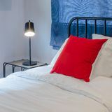 Red pillow on white bed with blue curtain and black lamp on tabl Royalty Free Stock Photo