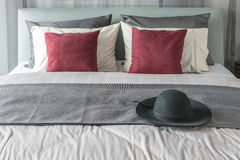 Red pillows and black hat on bed in modern bedroom. Design Royalty Free Stock Photo