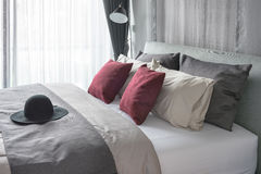 Red pillows and black hat on bed in modern bedroom. Design Stock Photos