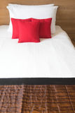 Red pillows. On white bed in bedroom Stock Photos