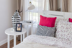 Red pillows on wooden white bed with modern lamp Royalty Free Stock Image