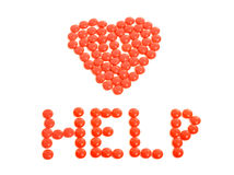Red pills arranged in heart shape with help sign. Royalty Free Stock Photos