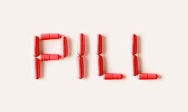 Red Pills capsules in shape of word Pill. Life concept isolated. Stock Photos