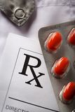 Red pills and patient list. On doctor's smock Royalty Free Stock Photography