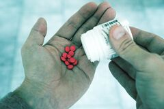 Red Pills in Person's Hand Royalty Free Stock Photo