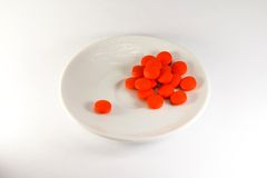 Red pills on a plate Royalty Free Stock Photos