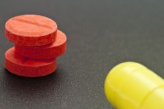 Pills II. Red pills stocked and a yellow one royalty free stock photo