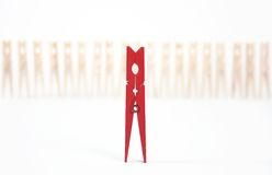 Red pin. A red clothespin in front of a line of wood clothespins Stock Image