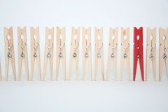 Red pin. One red clothespin in a line of regular ones Royalty Free Stock Photography