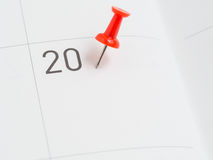 Red pin on 20 on calendar paper Stock Image