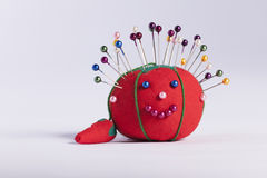 Red pin cushion with smily face on white background Stock Photo